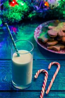 크리스마스 쿠키, 우유 잔, 카라멜 스틱, 화환을 태우는 가문비 나무 가지가있는 파란색 테이블의 이미지