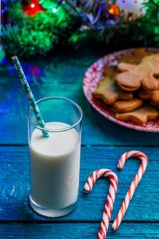 생강 비스킷, 우유 잔, 카라멜 스틱, 화환을 태우는 가문비 나무 가지가있는 파란색 테이블의 이미지