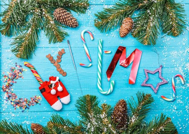Изображение синего стола с еловыми ветками, слово рождество из сладостей, бенгальский огонь, блестки, одежда санты