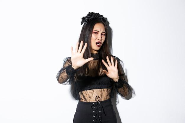 Изображение обеспокоенной и раздраженной азиатской женщины в элегантном готическом платье, поднимающей руки в защиту, гримасничающей от плоти камеры, просящей прекратить фотографировать ее, стоящую на белом фоне.