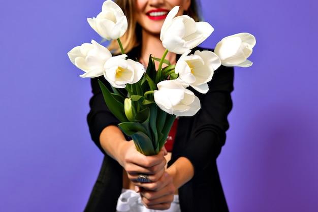 紫色の背景に分離された黒いジャケットの若いファッショナブルな女性の手に白いチューリップの花束の画像。