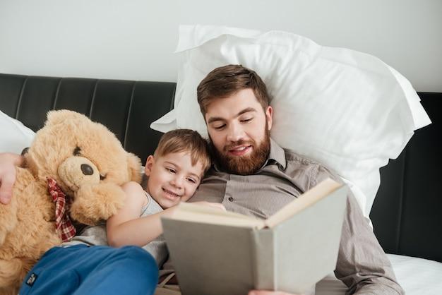 Изображение мальчика лежит дома в постели возле игрушки со своим бородатым отцом, читающим сказку.