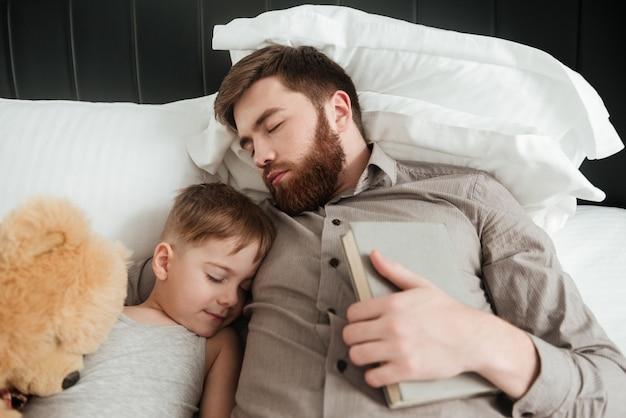 Изображение мальчика, спящего дома в постели рядом с игрушкой с его бородатым отцом, держащим книгу.