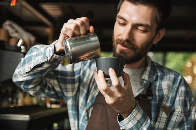 屋外のカフェや喫茶店で働いているときにコーヒーを作るエプロンを身に着けているブルネットのバリスタ男性の画像