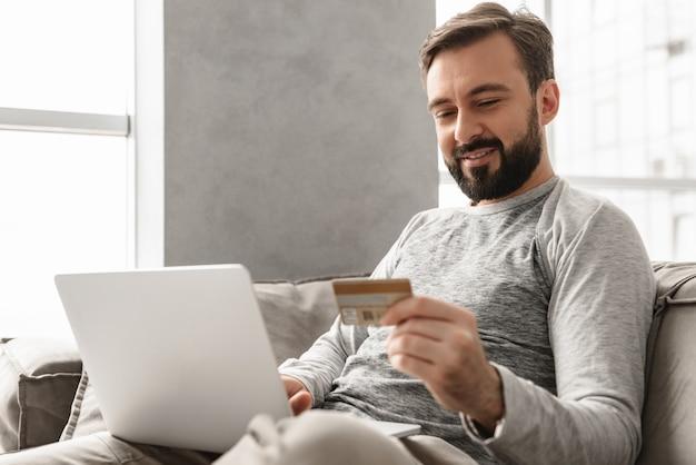 リビングルームのソファーに座っているカジュアルな服装で30代ブルネットの剃っていない男の画像とクレジットカードとノートブックで支払い取引を行う