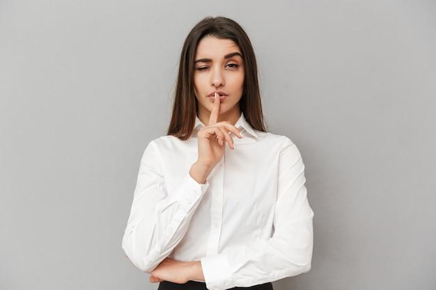 입술에 검지 손가락을 들고 회색 벽 위에 절연 침묵을 유지하도록 요구하는 공식적인 의류에 갈색 머리 여자 20 대의 이미지