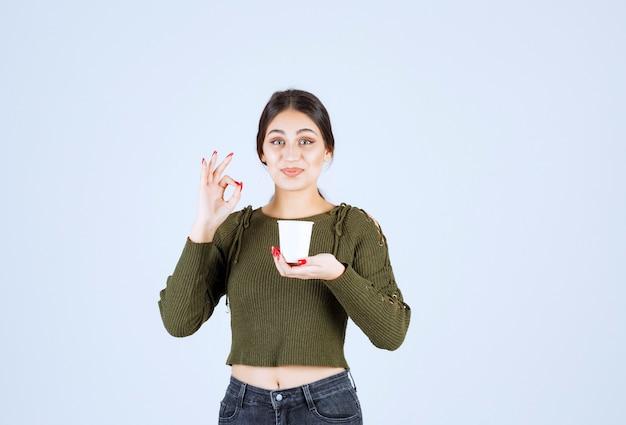 Изображение брюнетки женщины держа пластиковый стаканчик и давая одобренный знак.