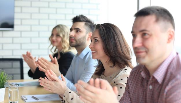 Изображение коллег по бизнесу, аплодирующих в конце конференции, сидя в очереди