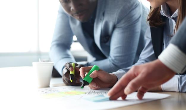 会議で書類を扱うビジネスマンの手の画像