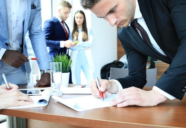 테이블에 앉아 새 프로젝트를 논의하는 비즈니스 팀의 이미지