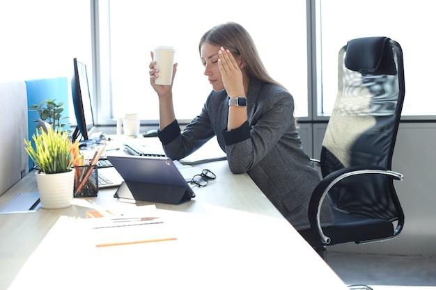 Изображение деловой женщины выглядят усталой, сидя на своем рабочем месте и держа в руке бумажный стаканчик.