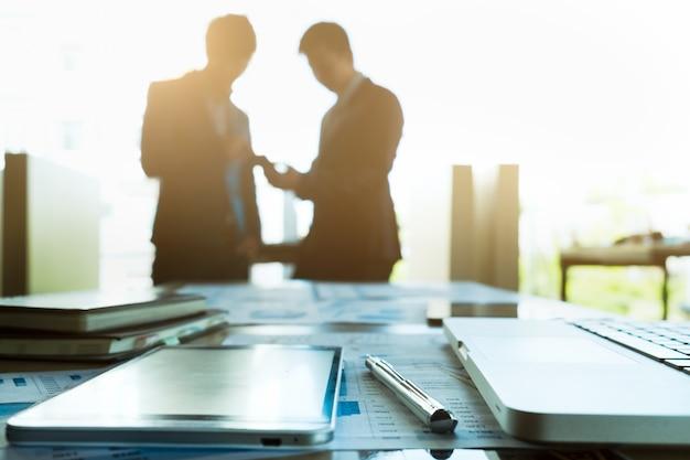 Изображение рабочего места бизнеса с партнерами команды, взаимодействующих на фоне.