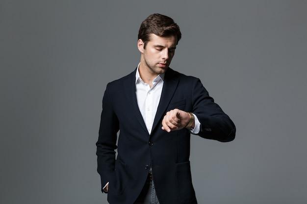 灰色の壁に隔離された腕時計を見て黒いジャケットを着た30代のビジネスライクな男の画像