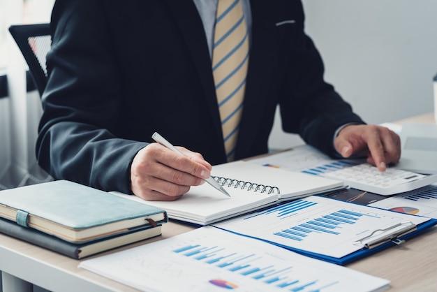 電卓を使用する準備ができてメモを取るためにペンを持っているビジネスマンの手の画像グラフはオフィスの机の上に置かれます。会計の概念。