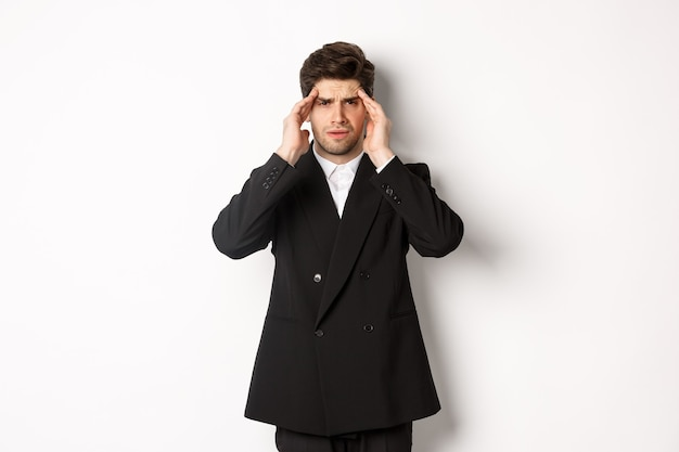 黒のスーツを着て、頭に触れて目がくらむように見え、痛みを伴う頭痛を感じ、白い背景の上に立っているビジネスマンの画像。