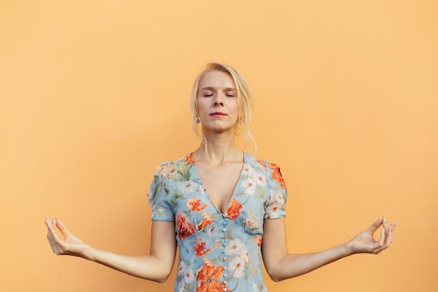 Изображение спокойной красивой женщины, медитирующей и держащей пальцы вместе, изолированные на оранжевом пастельном фоне.