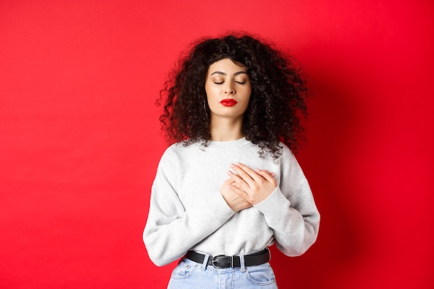 Изображение спокойной молодой женщины с кудрявой прической, закрытой глазами и держащей руки на сердце, хранящей теплые воспоминания, испытывающей ностальгию, стоящей на красном фоне