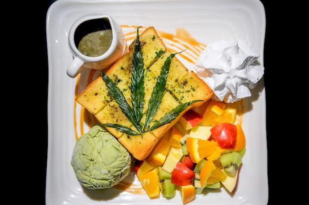 Изображение тоста меда конопли и смешанных фруктов в белой тарелке с черным фоном. медовые тосты с коноплей - это десерт, приготовленный из нарезанного кубиками хлеба. возьмите нож и отрежьте верхнюю часть хлеба.