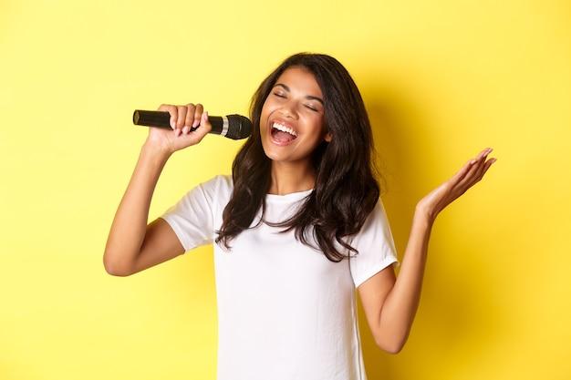 Изображение беззаботной афро-американской девушки, поющей в микрофон, счастливой улыбающейся, выступающей на желтом фоне