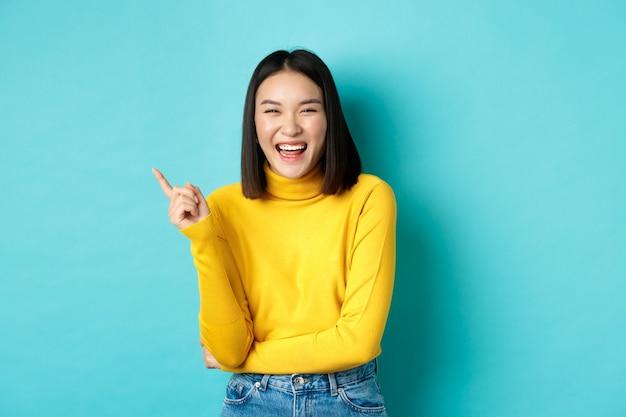 평온한 예쁜 한국 소녀 웃음과 행복을 찾고, 파란색에 서있는 왼쪽 상단 모서리 프로모션에서 손가락을 가리키는 이미지.