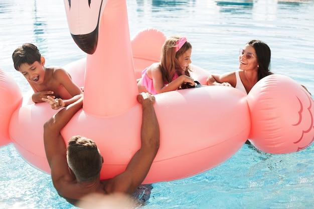 スパリゾートのホテルの外で、ピンクのゴムのリングが付いているプールで泳いでいる白人の美しい子供と親の画像