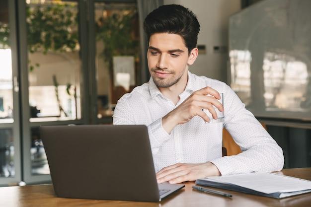 Изображение кавказского делового мужчины 30-х годов в белой рубашке, сидящего за столом и держащего стакан с водой во время работы на ноутбуке