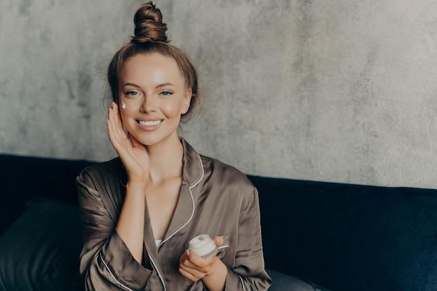 실크 잠옷을 입은 백인 쾌활한 여성의 이미지는 침실의 콘크리트 벽 배경 위에 격리된 보습 얼굴 크림을 부드럽게 바르면서 웃고 있습니다. 미용 및 스킨케어 개념