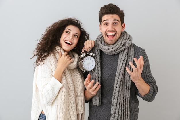 灰色の壁に隔離、目覚まし時計を保持しながら笑っている白人カップルの男性と女性の画像