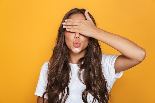黄色の壁に隔離された手で目を覆う長い髪の白人の素敵な女性20代の画像