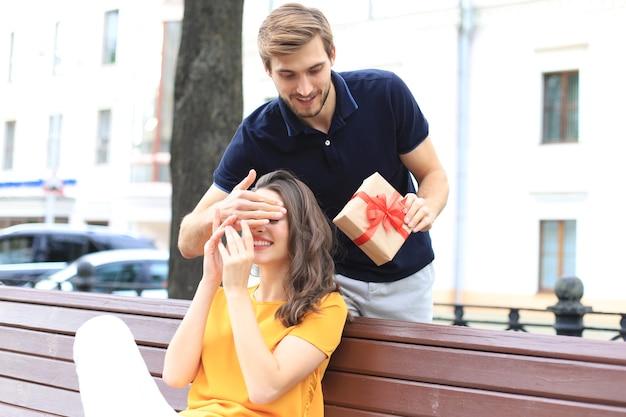 Изображение очаровательной взволнованной пары в летней одежде, улыбающейся и держащей подарочную коробку вместе, сидя на скамейке.