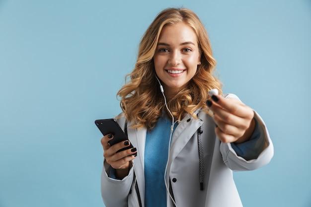Изображение очаровательной женщины 20-х годов в плаще, держащей мобильный телефон и показывающей наушники