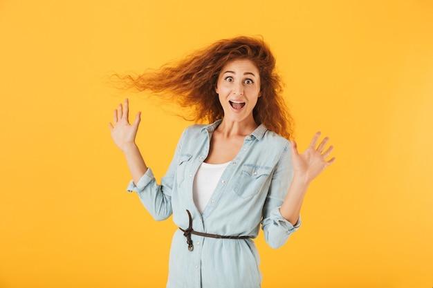 黄色の背景で隔離、驚きとカメラで身振りで示す巻き毛を持つ魅力的な若い女性の画像