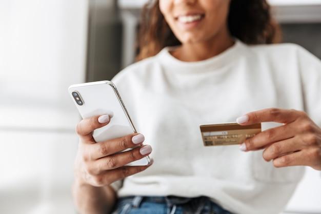 明るいリビングルームのテーブルに座っている間、携帯電話とクレジットカードを使用して陽気なアフリカ系アメリカ人の女の子の画像