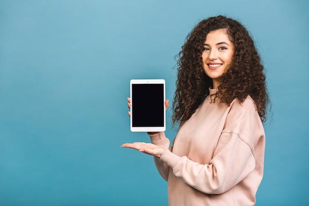 青い背景の上に分離されたタブレットコンピューターのディスプレイを示す陽気な驚いた若い巻き毛の白人女性の画像。