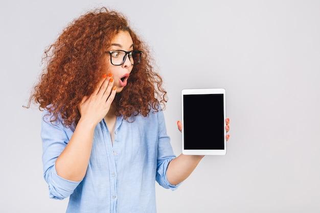 タブレットコンピュータのディスプレイを示す陽気な驚いた若い巻き毛の女性の画像