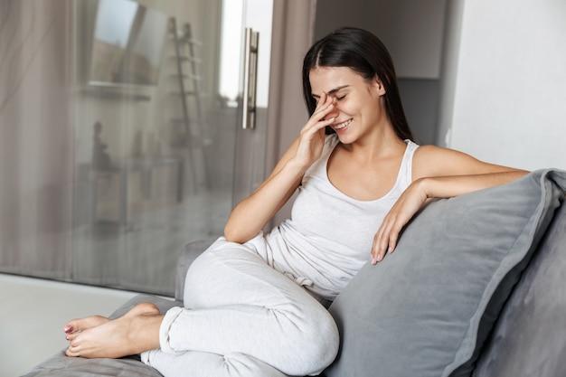 Изображение веселой красивой молодой женщины, сидящей на диване в помещении у себя дома.