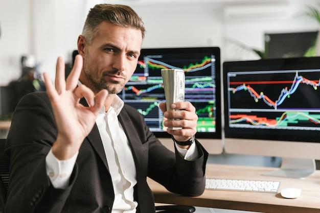 Изображение веселого бизнесмена 30-х годов в костюме, держащего пачку денег во время работы в офисе с графикой и диаграммами на компьютере