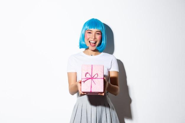 ピンクの紙に包まれたギフトを贈り、何かを祝福し、立っている、青いパーティーウィッグの陽気なかわいいアジアの女の子の画像。