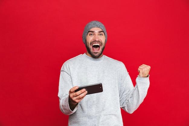 고립 된 휴대 전화를 사용하는 동안 기쁨 캐주얼에 쾌활한 남자 30 대의 이미지