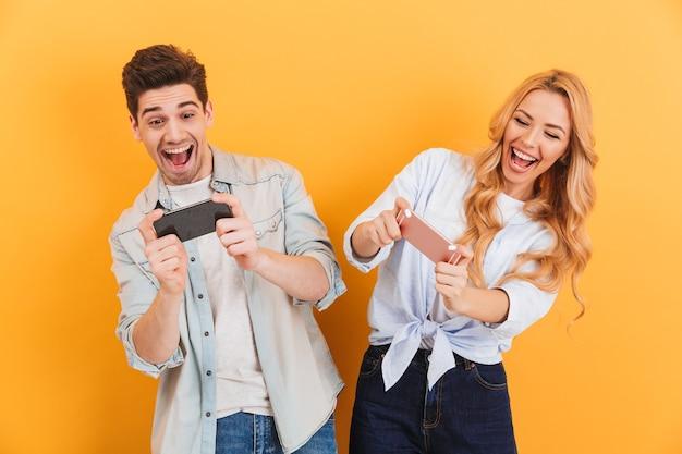 쾌활한 남자와 여자가 함께 휴대 전화에서 비디오 게임을하는 이미지