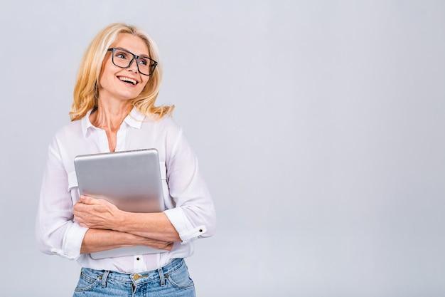 Изображение жизнерадостной зрелой деловой женщины, стоящей изолированной на белом фоне с помощью портативного компьютера. портрет улыбающегося старшего дама, держащего портативный компьютер.
