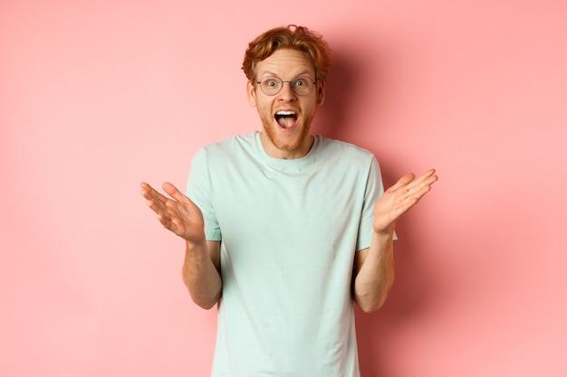 빨간 머리를 가진 쾌활한 젊은 수염 난 남자의 이미지, 안경을 쓰고, 좋은 소식을 기뻐하며, 손을 옆으로 펼치고, 분홍색 배경 위에 서서 축하합니다.