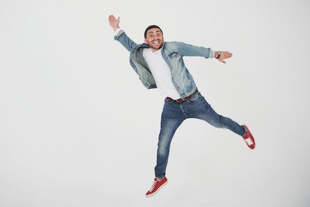 Образ веселый молодой человек случайный одет прыжки над белым