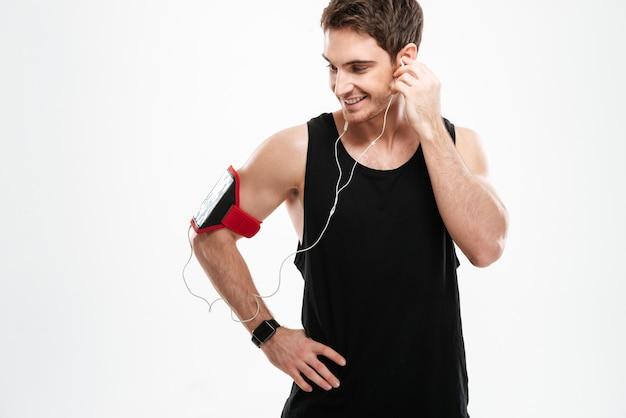 Изображение веселого молодого человека, одетого в черную футболку, стоящего над белой стеной, слушая музыку.