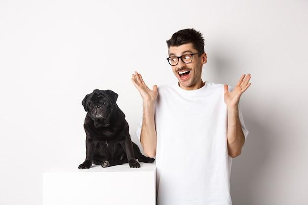 Изображение веселого ликования молодого человека, смотрящего на мопса милой черной собаки и усмехаясь, стоя над белой предпосылкой.