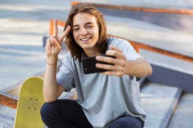 スケートボードで公園に座っている陽気な若いスケーターの男の画像は、平和のジェスチャーで携帯電話で自分撮りを取ります。
