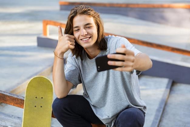 スケートボードを持って公園に座っている陽気な若いスケーターの男の画像は、親指を立てて携帯電話で自分撮りを取ります。