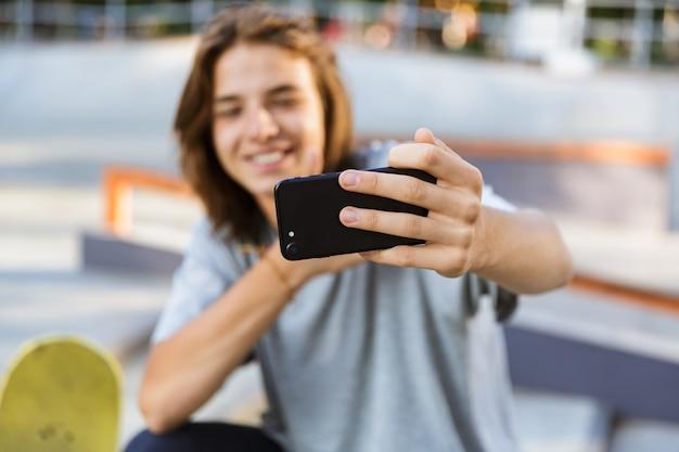スケートボードを持って公園に座っている陽気な若いスケーターの男の画像は、携帯電話で自分撮りを取ります。