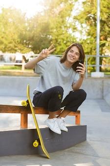 平和のジェスチャーを示す携帯電話を使用してスケートボードで公園に座っている陽気な若いスケーターの男の画像。
