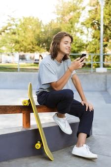 陽気な若いスケーターの男の画像は、携帯電話を使用してスケートボードで公園に座っています。